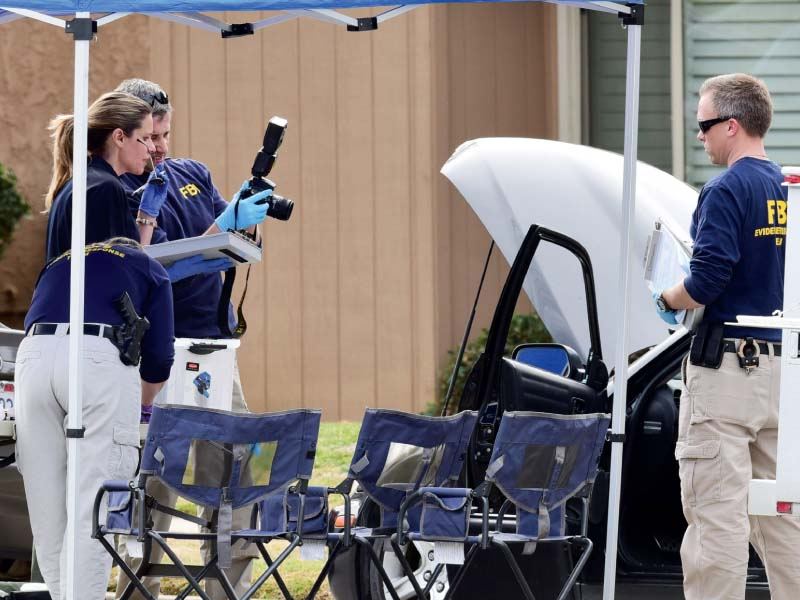 fbi agents examine a car outside a house in redlands california photo afp
