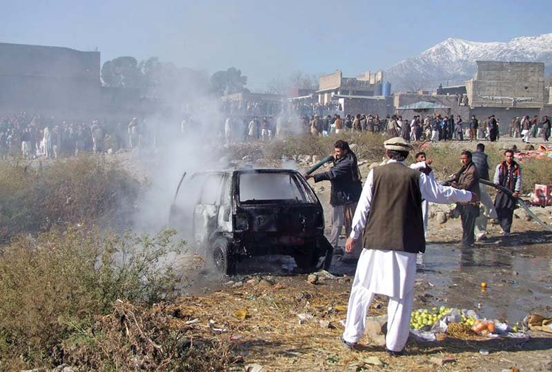 firefighters extinguish a fire in a vehicle at the bomb site in parachinar photo afp