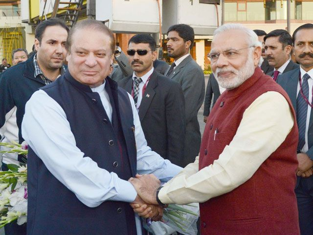 PM Nawaz Sharif shakes hands with his Indian counterpart Narendra Modi upon latter's arrival at the Allama Iqbal International Airport in Lahore on December 25, 2015. PHOTO: PID
