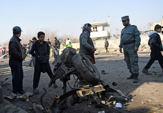 an afghan policeman looks at the wreckage of a car that was used in a suicide car bomb near kabul 039 s international airport on december 28 2015 photo afp