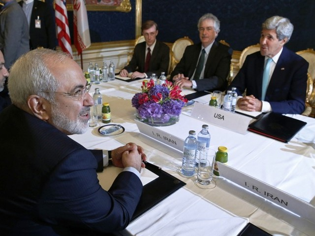 Iran's Foreign Minister Mohammad Javad Zarif (L) meets with US Secretary of State John Kerry (R) during talks between the foreign ministers of the six powers negotiating with Tehran on its nuclear programme, in Vienna, on July 13, 2014. PHOTO: AFP