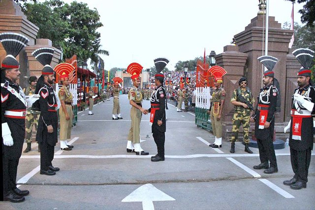 Personnel of Pakistan and Indian Rangers shake hands during the flag-lowering ceremony at the Wagah border on September 13, 2015. PHOTO: APP