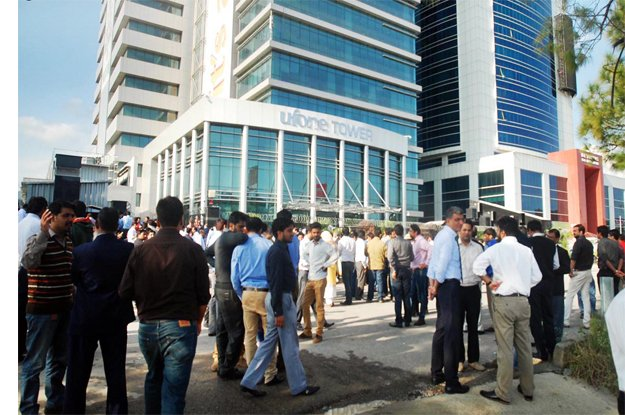 Office workers seen outside a high-rise building after 5.8 magnitude Earthquake jolted the areas of Pakistan and Afghanistan. PHOTO: ONLINE