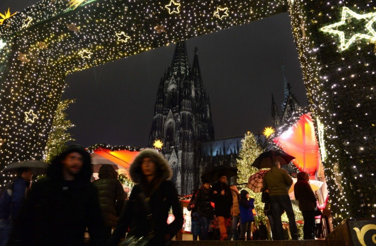 people walk through the entrance of a market in cologne germany during new year 039 s eve photo afp