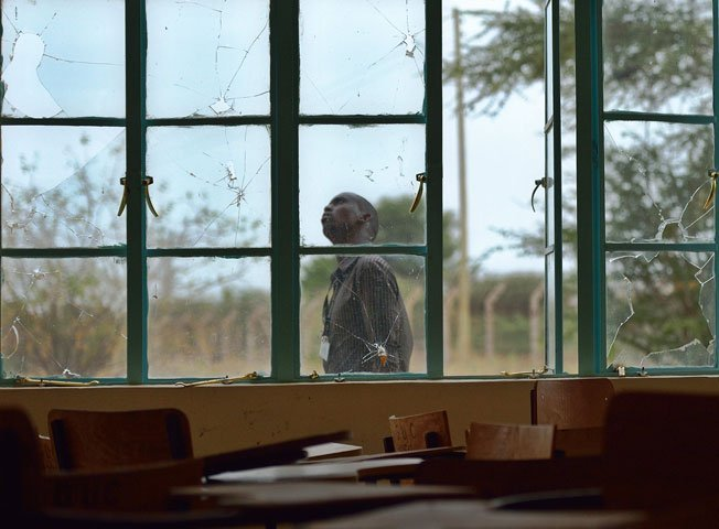 A man walks outside a lecture hall with bullet-shattered window panes in Garissa university on January 11, 2016. PHOTO: AFP