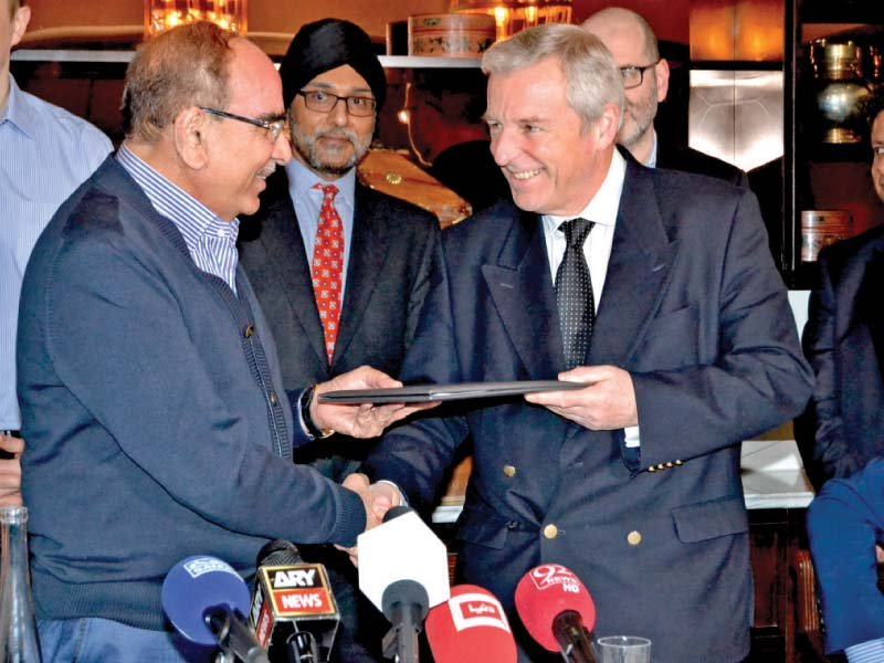 bahria town chief malik riaz and harley street clinic s dr richard gullen exchange documents after signing the agreement photo pr