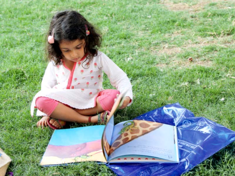 a little girl flips through her book in the beach luxury lawn at the literature festival on friday