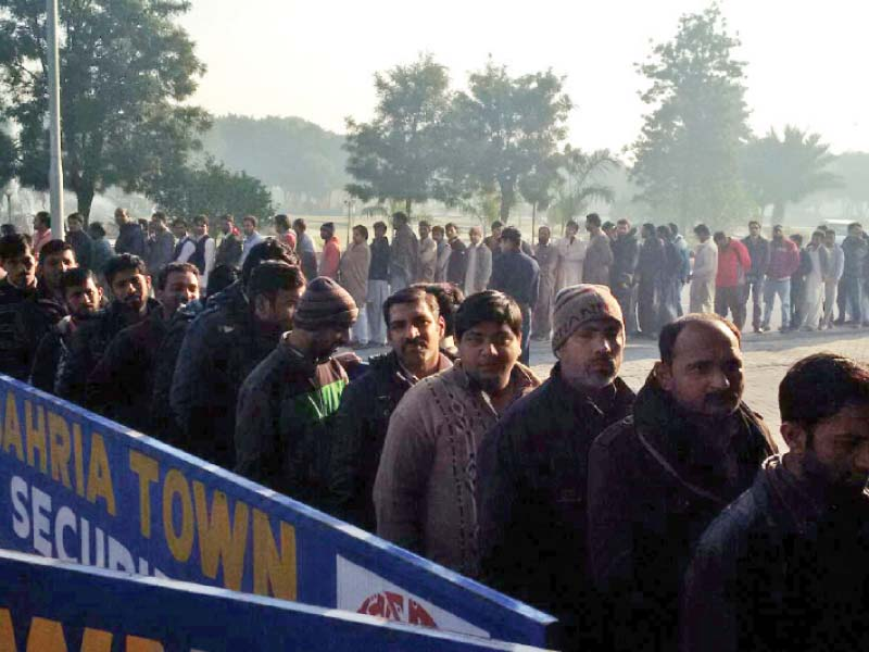 people wait in queue outside a bahria town office photo express