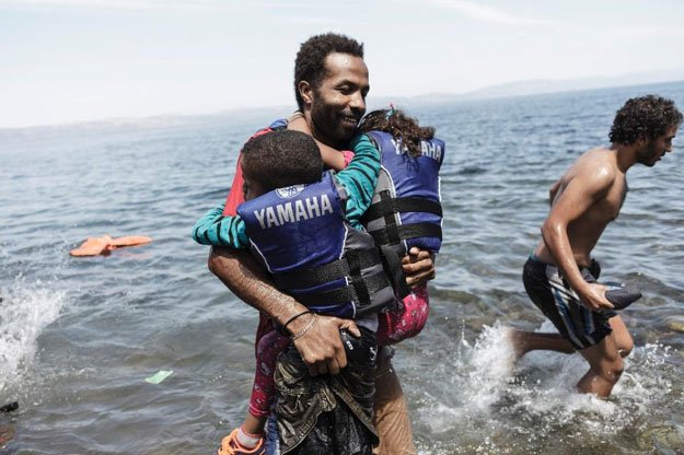 A migrant carries his two children as he gets off an inflatable boat after arriving on the Greek island of Lesbos after crossing the Aegean sea from Turkey on August 14, 2015 PHOTO: AFP