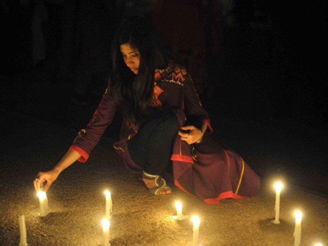 a pakistani girl lights candles in front of parliament house to mark the sixth global earth hour in islamabad on march 31 2012 photo afp