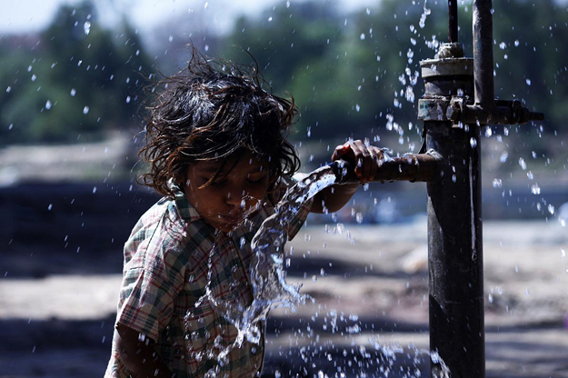 a girl drinking water from a hand pump on the eve of world water day photo online