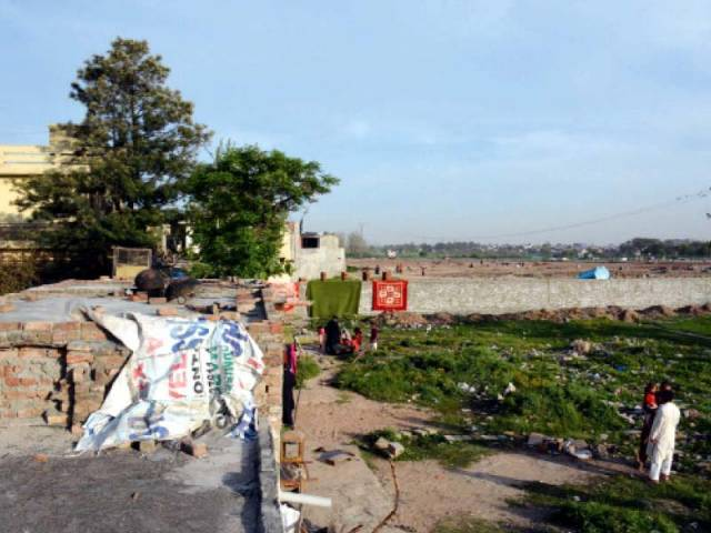 a view of the boundary wall of the under construction shahbaz sharif park in the distance that has blocked residents access to their homes in dhoke kaku shah rawalpindi photo express