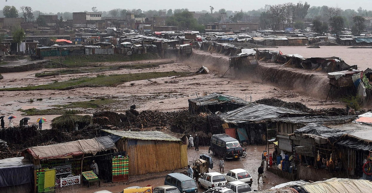 flood waters rush through a market area as vendors and resident scramble to save their possessions on the outskirts of peshawar on april 3 2016 photo afp