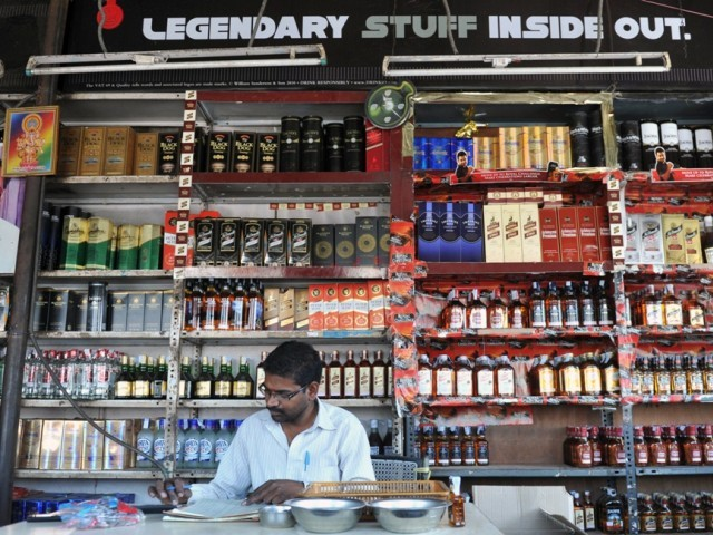 an indian employee writes down stock at an alcohol store in hyderabad photo afp