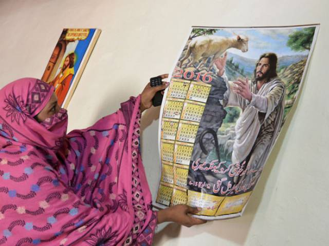 newly recruited christian tribal police woman naila jabbar hangs a calendar on a wall at her home in landi kotal in khyber district on april 8 2016 photo afp