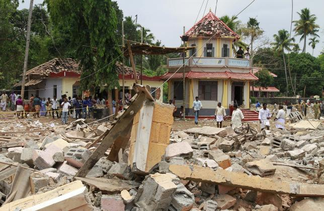 people stand next to debris after a broke out at a temple in kollam in the southern state of kerala india april 10 2016 photo reuters