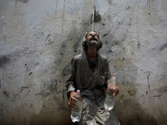 a man cools off under a public tap in karachi photo reuters