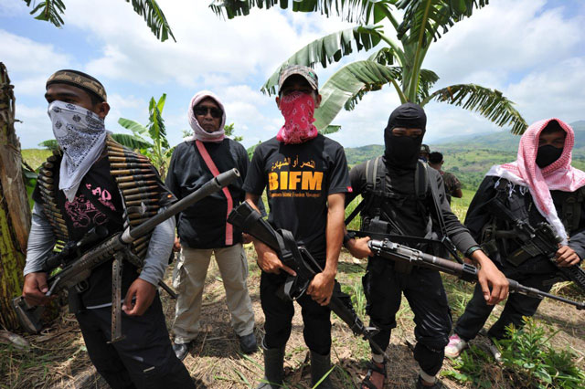 this file photo shows members of a breakaway muslim separatist group stand guard during a clandestine press conference in the town of datu unsay sothern maguindanao province in the philippines on august 28 2011 photo afp