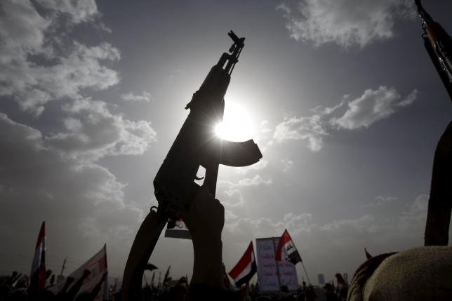 a houthi follower rises a weapon as he attends a rally marking one year of saudi led air strikes in yemen 039 s capital sanaa march 26 2016 photo reuters