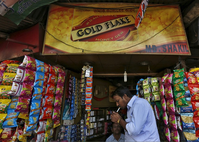 a man lights a cigarette in front of a kiosk in kolkata india april 7 2016 photo reuters