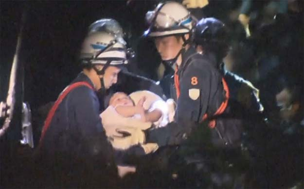 the baby is carried away by rescue workers photo aptn via telegraph