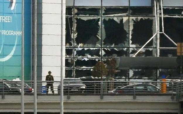 a soldier stands near broken windows after explosions at zaventem airport near brussels belgium march 22 2016 reuters