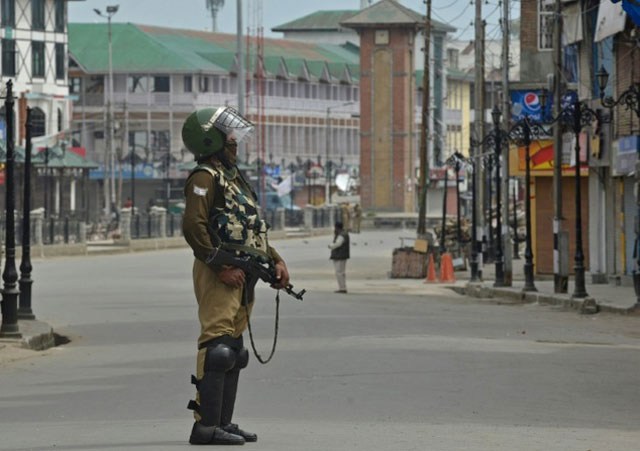 an indian paramilitary trooper stands guard during a tense curfew in srinagar on april 15 2016 photo afp