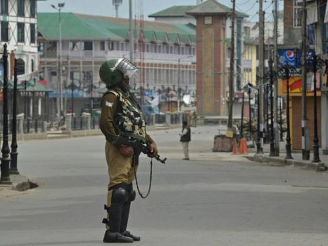 an indian paramilitary trooper stands guard during a tense curfew in srinagar photo afp
