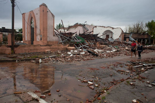 people walk past the remains of a church hit by a tornado in dolores uruguay on april 16 2016 photo afp