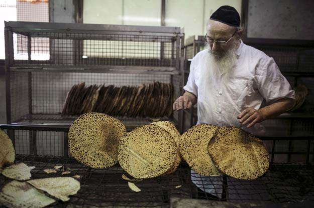 an ultra  orthodox jew inspects freshly baked matza the traditional unleavened bread eaten during the jewish holiday of passover in bnei brak in this file photo taken march 30 2015 photo reuters
