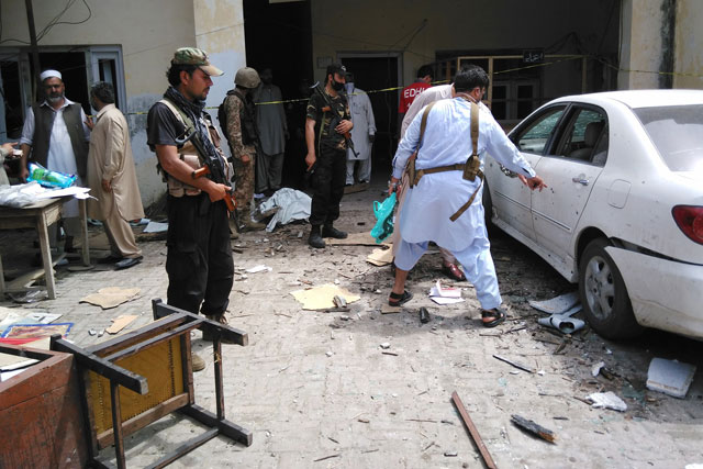 security officials inspect the site of a suicide bomb attack at mardan 039 s excise and taxation department on april 19 2016 photo afp