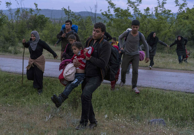 syrian refugees cross a road with their children while on the run in a forest in macedonia after illegally crossing greek macedonian border near the city of gevgelija on april 23 2016 photo afp