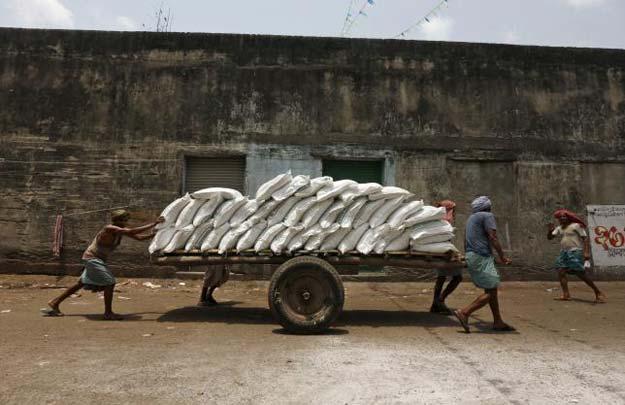 labourers push a handcart loaded with sacks of sugar at a wholesale market in kolkata india april 26 2016 photo reuters