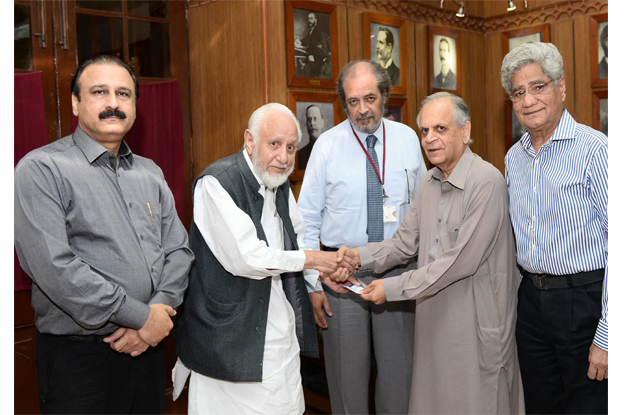 prof zaheer ahmed siddiqui handing over the cheque to vice chancellor hassan amir shah during a ceremony held at the syndicate committee room photo express