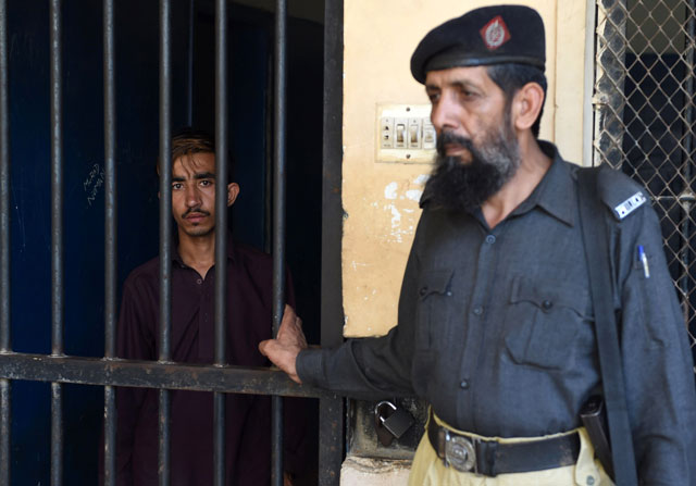hayat khan an alleged killer of his sister l stands in a lockup at a police station in karachi on april 28 2016 photo afp