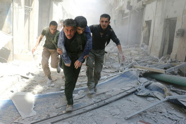 syrians evacuate an injured man following an air strike on a rebel held neighbourhood in the northern syrian city of aleppo on april 29 2016 photo afp