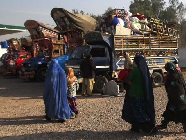 an afghan refugee family walks past trucks loaded with their belongings as they prepare to go back to afghanistan with others at the unhcr office on the outskirts of peshawar february 13 2015 photo reuters