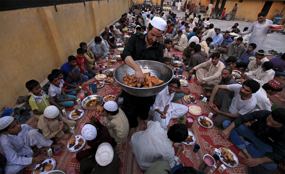 a volunteer carries food trays for others before breaking fast at memon mosque in karachi photo reuters