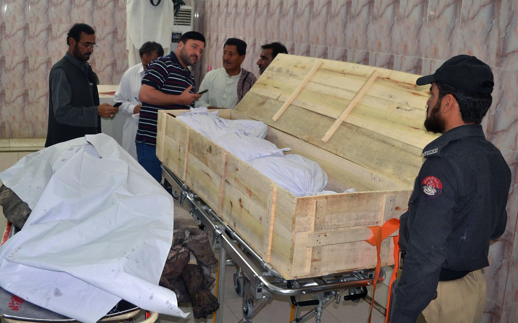 Security officials and hospital staff stand next to unidentified dead bodies placed on stretchers at a morgue in a hospital in Quetta on May 22, 2016, which were brought following a drone strike in the remote town of Ahmad Wal in Balochistan that targeted Afghan Taliban chief Mullah Akhtar Mansour. PHOTO: AFP