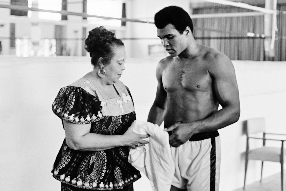 """This file photo taken on October 27, 1974 shows US boxing heavyweight champion Muhammad Ali (born Cassius Clay) standing with her mother Odessa Grady Clay during a training session three days before the heavy weight world championship in Kinshasa.  Boxing icon Muhammad Ali died on Friday, June 3, a family spokesman said in a statement. """"After a 32-year battle with Parkinson s disease, Muhammad Ali has passed away at the age of 74,"""" spokesman Bob Gunnell said. PHOTO: AFP"""