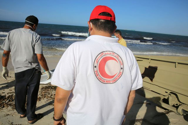 Libyan Red Crescent workers stand beside the body of a migrant who died after a boat sank off the coastal town of Zuwara west of Tripoli, in Libya  June 3, 2016. PHOTO: REUTERS