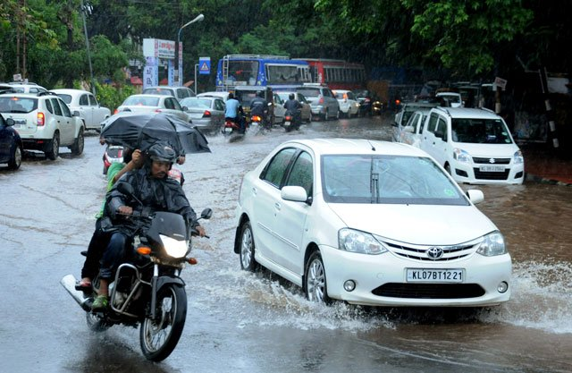 This file photograph taken on June 8, 2016, shows Indian commuters as they make their way along a waterlogged road during heavy monsoon rains in Kochi. PHOTO: AFP / FILE