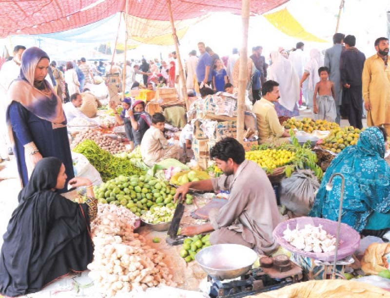 a woman checks fruit at a ramazan bazaar photo express