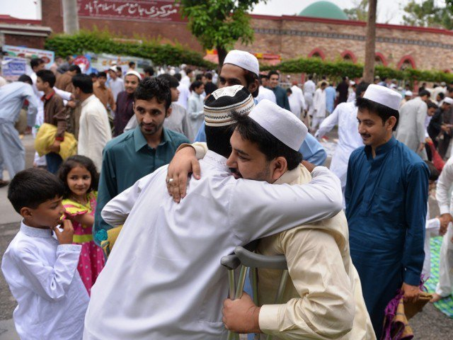 people exchange eid greetings after offering eidul fitr prayers in islamabad on july 29 2014 photo afp