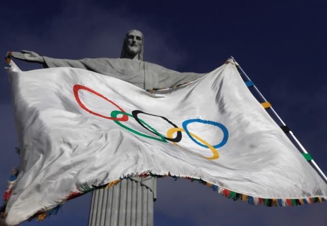 """The Olympic Flag flies in front of """"Christ the Redeemer"""" statue. PHOTO: REUTERS"""