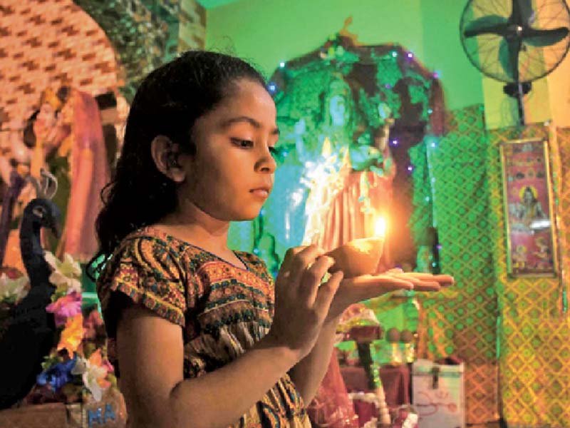 a child holds an earthen lamp as she celebrates diwali at a temple hindus across the globe make merry at the festival of lights decorating their homes and setting off fireworks photo inp