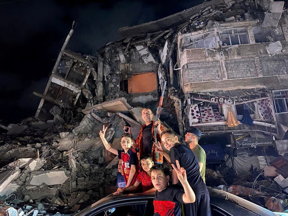 People gesture near the rubble of a damaged building as Palestinians celebrate in the streets following a ceasefire, in Gaza City May 21, 2021. PHOTO: REUTERS