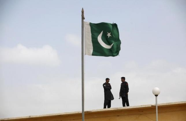 a-pakistani-flag-flies-on-a-mast-as-paramilitary-frontier-corps-soldiers-talk-while-guarding-at-karachi-039-s-district-malir-prison-august-23-2013-photo-reuters