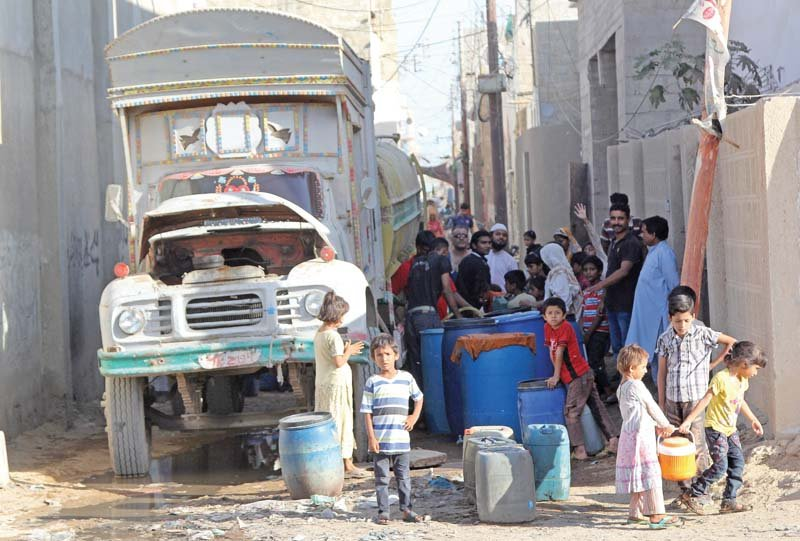 families buy water from a tanker due to shortage of the essential commodity in korangi photo aysha saleem express