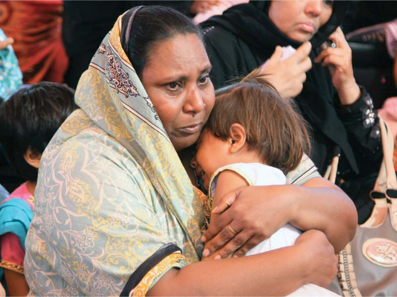 a woman who lost a relative in the factory fire grieves at the incident s anniversary in 2015 photo file